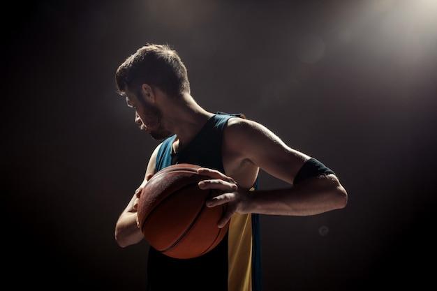 Profili il punto di vista di una palla del canestro della tenuta del giocatore di pallacanestro sulla parete nera