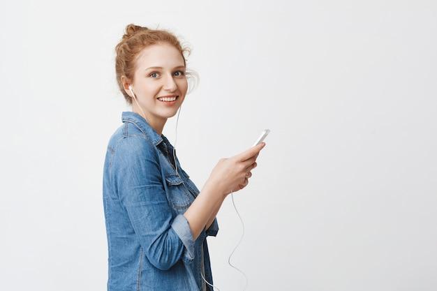Profili il ritratto dell'adolescente adorabile della testarossa con capelli pettinati in panino, tenendo lo smartphone e la musica d'ascolto in cuffie