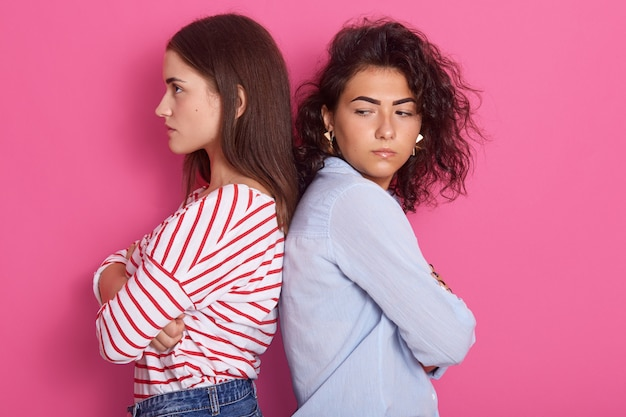 Profili il ritratto di belle ragazze con capelli scuri che aggrottano le sopracciglia nel dispiacere, indossando camicie casual, tenendo le braccia conserte, non parlare tra di loro, in posa isolato su studio rosa