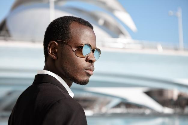 Profili il ritratto di giovane bello responsabile sicuro dalla pelle scura che indossa gli occhiali da sole alla moda e il vestito nero che stanno all'aperto con l'edificio per uffici moderno