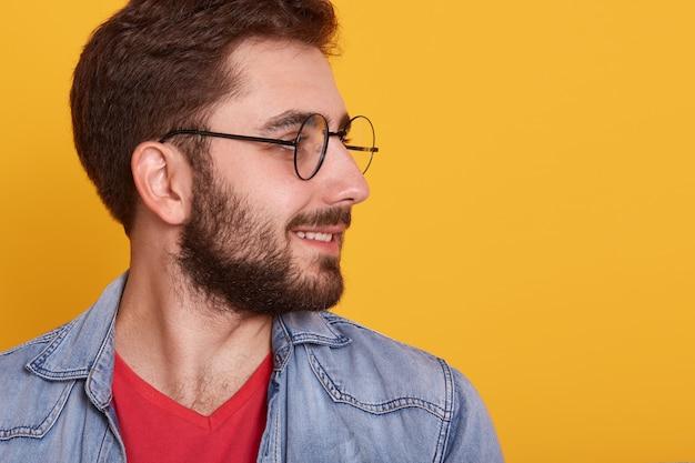 Profili il ritratto sulla testa girata e la barba ben rifinita dell'uomo handsopme con gli occhiali, indossa camicia rossa ed elegante giacca di jeans