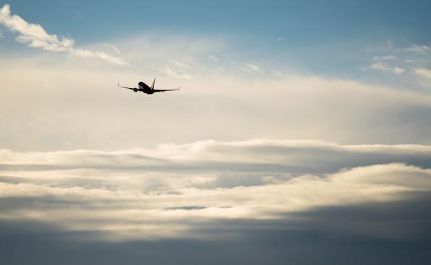 Profili il volo dell'aeroplano nei bordi del cielo dalla nuvola blu