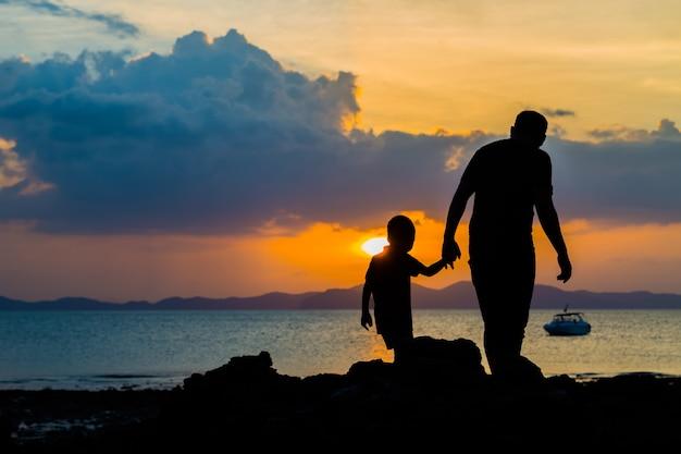 Profili l'immagine del padre e del figlio alla spiaggia prima del fondo del tramonto