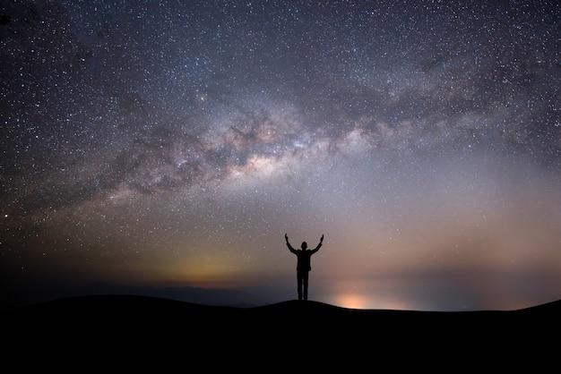 Profili l'uomo di successo sulla cima della collina su uno sfondo con le stelle