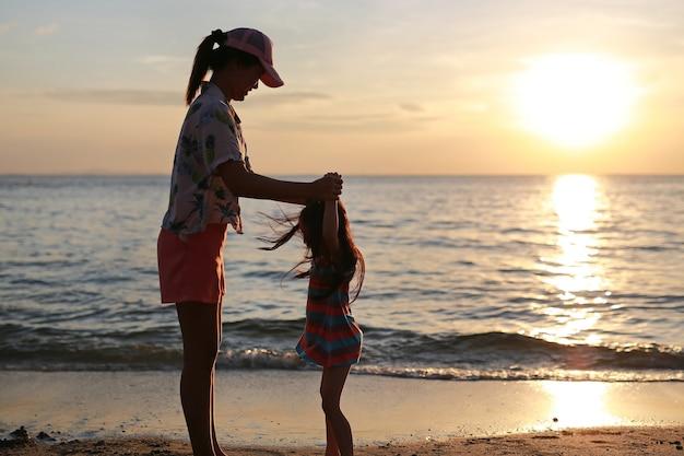 Profili la madre asiatica e la figlia che stanno e che giocano sulla spiaggia al tramonto.