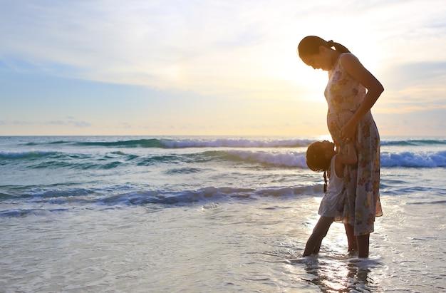 Profili la madre incinta che abbraccia la figlia che si rilassa sulla spiaggia al tramonto.