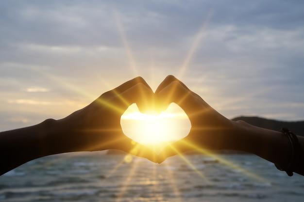 Profili la mano nella forma del cuore con alba sui precedenti della spiaggia