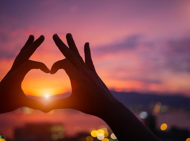 Profili la mano per essere una forma del cuore durante il fondo del tramonto.