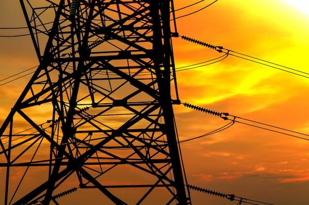 Profili la nuvola rossa del mucchio di notte del palo elettrico di potere sul cielo