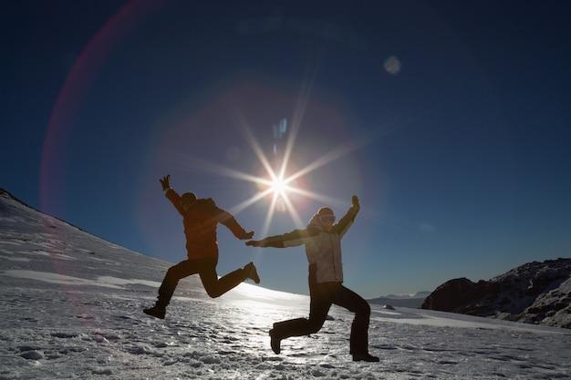 Profili le coppie che saltano sulla neve contro il sole ed il cielo blu