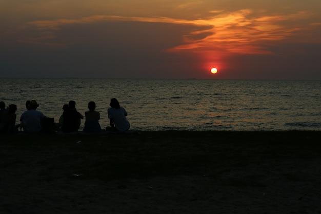 Profili tutta la gente che incontra il cielo di tramonto di sguardo sulla spiaggia