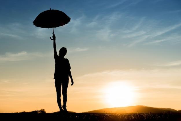 Profili una giovane donna felice con l'ombrello al tramonto