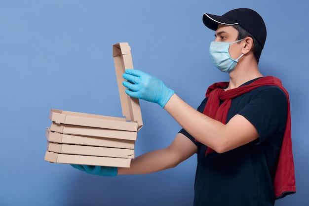 Profilo del corriere che indossa maglietta, maglione sopra le spalle, berretto, maschera protettiva e guanti in lattice, il fattorino apre la scatola con ordine e lo spinge al cliente