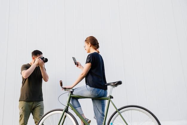 Profilo del fotografo alla moda che prende una foto di bello modello sorridente facendo uso di un telefono cellulare mentre sedendosi sulla bici. all'aperto.
