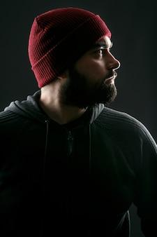 Profilo del giovane barbuto in cappello rosso in piedi su sfondo grigio