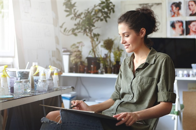 Profilo di affascinante giovane designer femminile professionale vestita in abbigliamento elegante godendo il processo di creazione, tenendo la matita, schizzi su tablet di grandi dimensioni. concetto di persone, creatività, arte e design