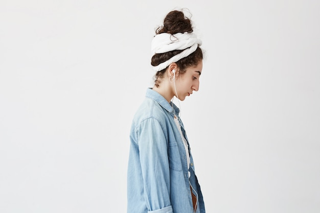 Profilo di bella donna con i capelli mossi in panino, vestita in camicia di jeans su camicia bianca, con auricolari bianchi, ascolto delle canzoni preferite, musica, in posa contro il muro bianco