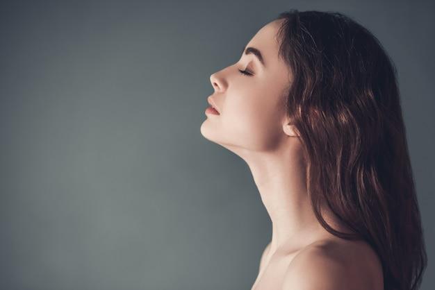 Profilo di bella ragazza sensuale con spalle nude.