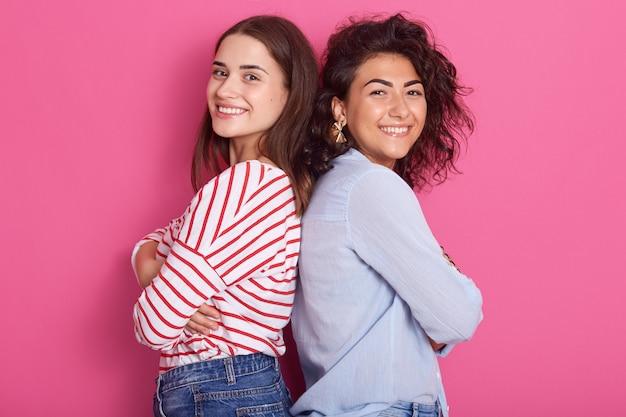 Profilo di due ragazze adulte attraenti in piedi schiena contro schiena, indossando abiti casual, guardando sorridendo direttamente alla telecamera, in posa isolato su rosa