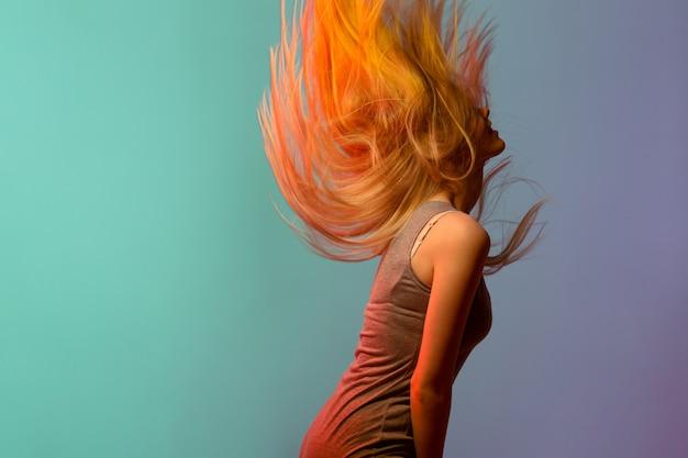 Profilo di giovane donna bionda graziosa che scuote i suoi capelli