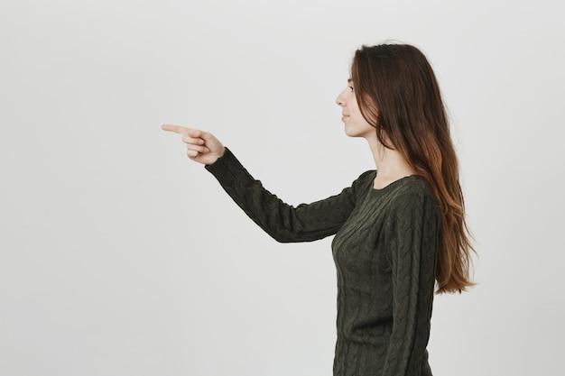 Profilo di giovane donna graziosa che punta il dito sinistro, raccolta o scelta