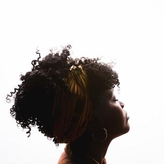 Profilo di giovane femmina afroamericana riccia su sfondo bianco