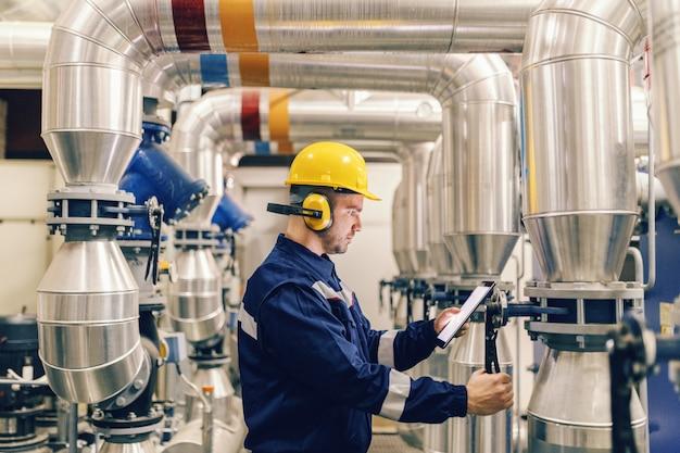 Profilo di giovane lavoratore caucasico che stringe la valvola e che utilizza compressa mentre stando nell'impianto di riscaldamento.