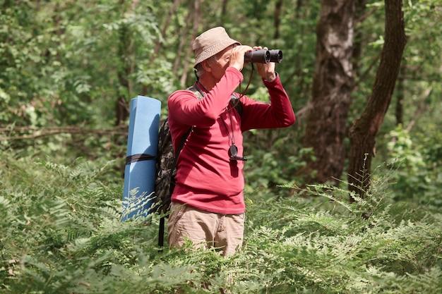 Profilo di hicker attivo guardando attraverso il binocolo, con la bussola sul collo, con felpa e pantaloni