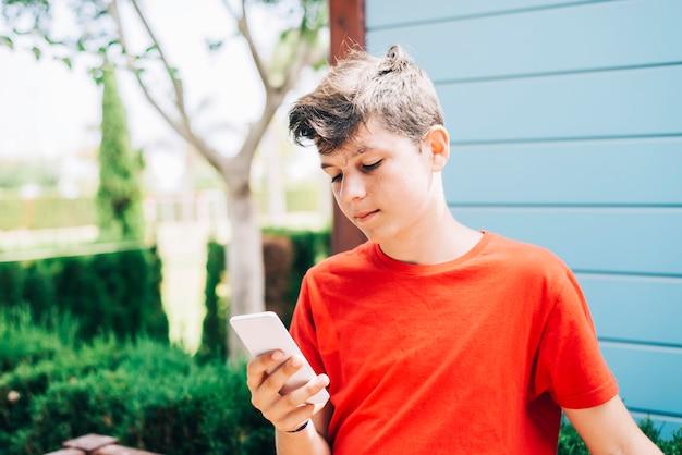 Profilo di un adolescente maschio maschio felice che manda un sms su uno smart phone