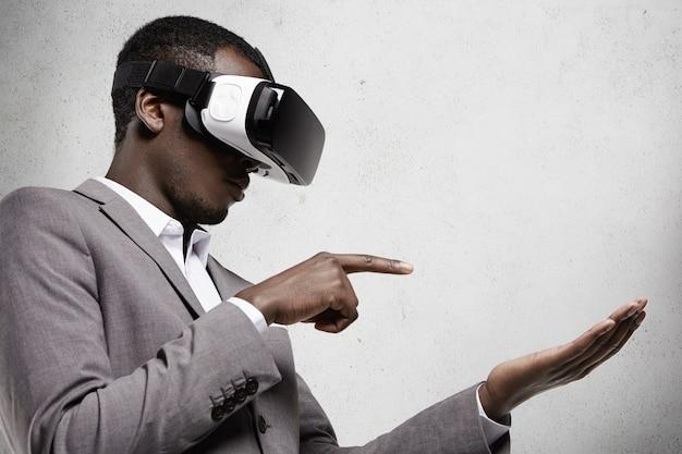 Profilo di un uomo d'affari africano in abito grigio che indossa occhiali 3d auricolare in ufficio, gesticolando come se si tenesse un gadget sul palmo della mano e toccandolo con il dito indice durante la riproduzione di videogiochi
