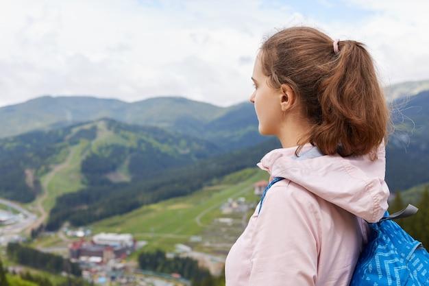 Profilo di viaggiatore esperto con coda di cavallo che indossa zaino e giacca rosa, godendo del paesaggio montano