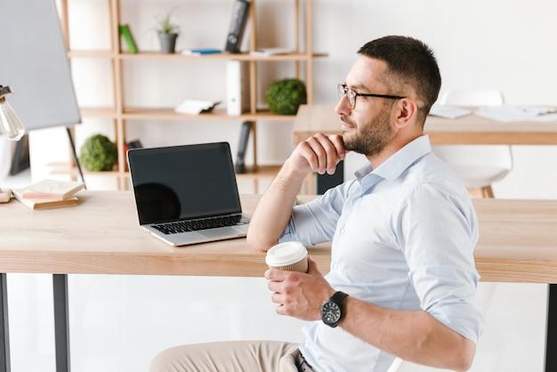 Profilo uomo ufficio diligente 30s in camicia bianca seduto a tavola e bere caffè da asporto, mentre si lavora al computer portatile nel centro business