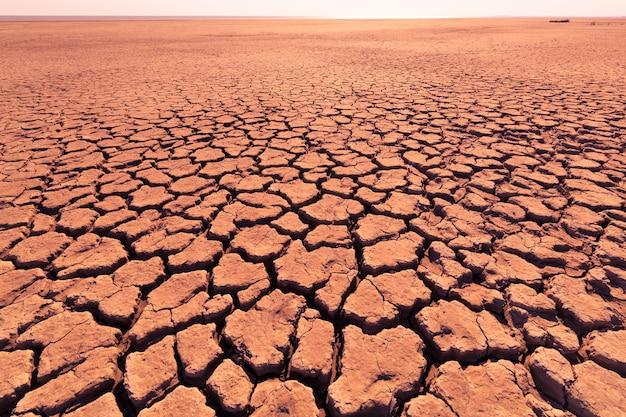 Profonde crepe nella terra rossa come simbolo del clima caldo e della siccità