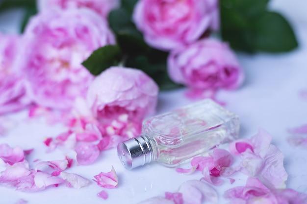 Profumo con fiori rosa su superficie chiara