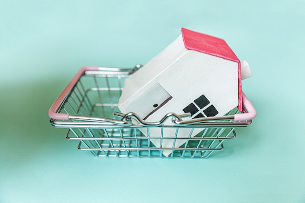 Progetta semplicemente con la casa del giocattolo in miniatura bianca e il cestino della spesa della drogheria del supermercato isolato sulla parete blu. assicurazione sulla proprietà ipotecaria casa dei sogni concetto copia spazio