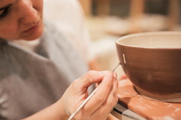 Progettazione del disegno della mano del vasaio femminile sulla superficie esterna della ciotola con lo strumento