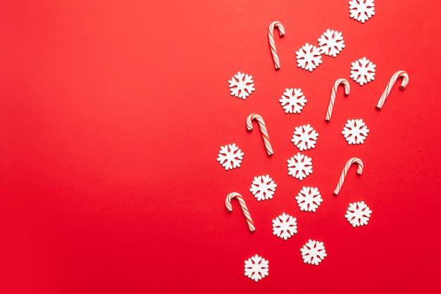 Progettazione del nuovo anno di natale con i fiocchi di neve bianchi con molti bastoncini di zucchero su rosso pastello