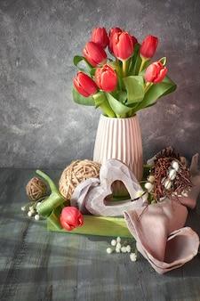 Progettazione della cartolina d'auguri di pasqua con il mazzo di tulipani rossi su rustico con le decorazioni di pasqua, copyspace
