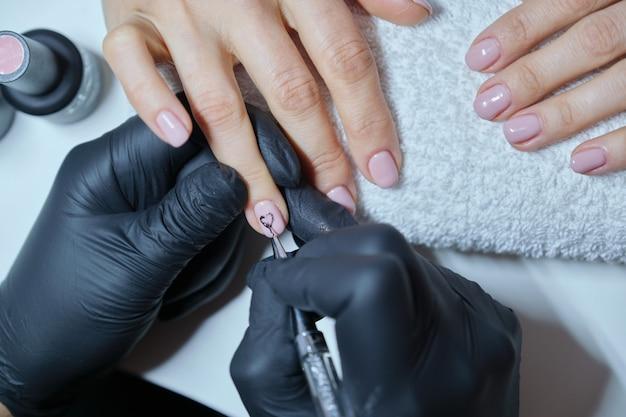 Progettazione di arte della pittura dell'estetista del primo piano sulle unghie.