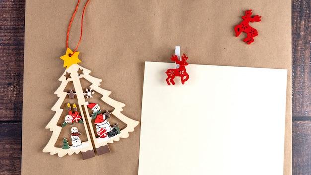 Progettazione in bianco della cartolina d'auguri in bianco di buon natale su un fondo del mestiere.