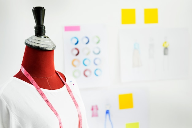Progettazione indumento su manichino manichino rosso con nastro di misura in studio stilista di moda, design creativo e concetto artistico