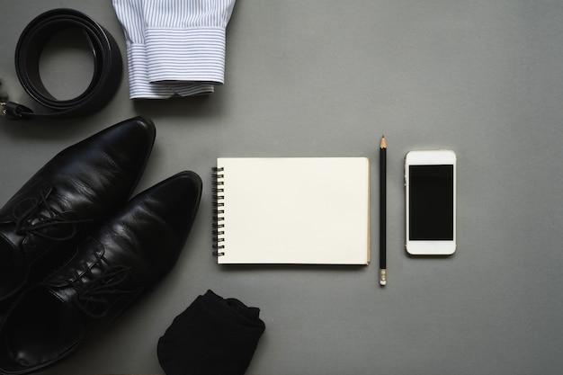 Progettazione piana di disposizione dei vestiti dell'uomo d'affari con il taccuino e lo smartphone in bianco su fondo grigio