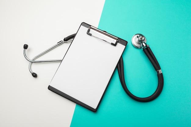 Progettazione piana di disposizione dello stetoscopio e del cuscinetto in bianco della lavagna per appunti con per il concetto medico.