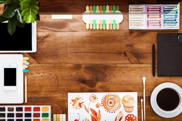 Progetti il concetto creativo del worktable, pitture del computer sullo scrittorio di legno marrone