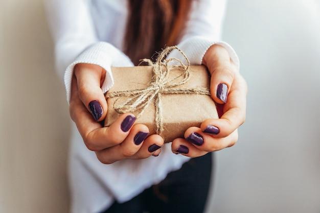 Progetti semplicemente il contenitore di regalo marrone d'annata della tenuta femminile della mano della donna isolato