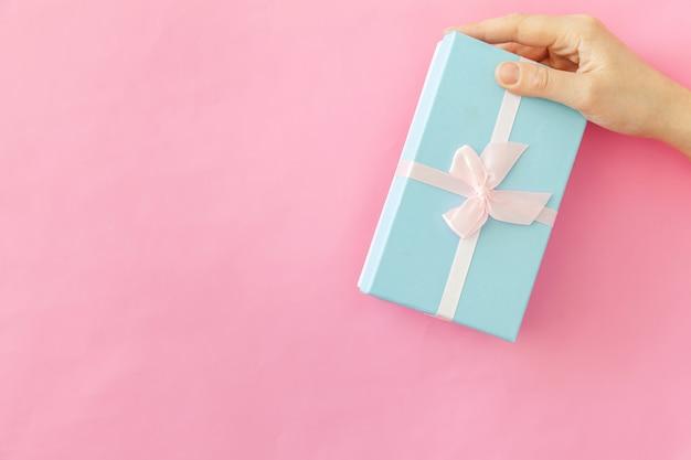 Progetti semplicemente la mano femminile della donna che giudica il contenitore di regalo blu isolato su fondo d'avanguardia variopinto pastello rosa