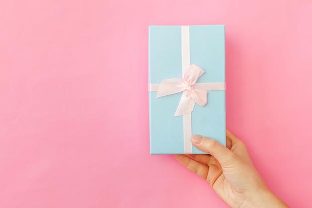 Progetti semplicemente la mano femminile della donna che tiene il contenitore di regalo blu isolato su d'avanguardia variopinto pastello rosa