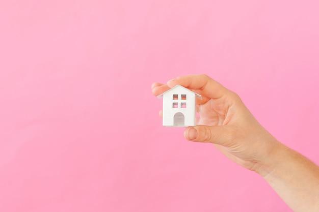 Progetti semplicemente la mano femminile della donna che tiene la casa bianca miniatura del giocattolo isolata su fondo d'avanguardia variopinto pastello rosa