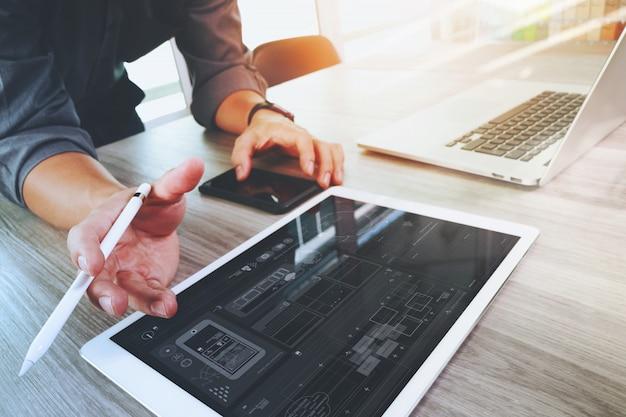 Progettista del sito web che lavora compressa digitale e computer portatile e diagramma di progettazione digitale