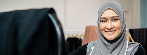 Progettista di donna musulmana asiatica nel suo negozio di sartoria